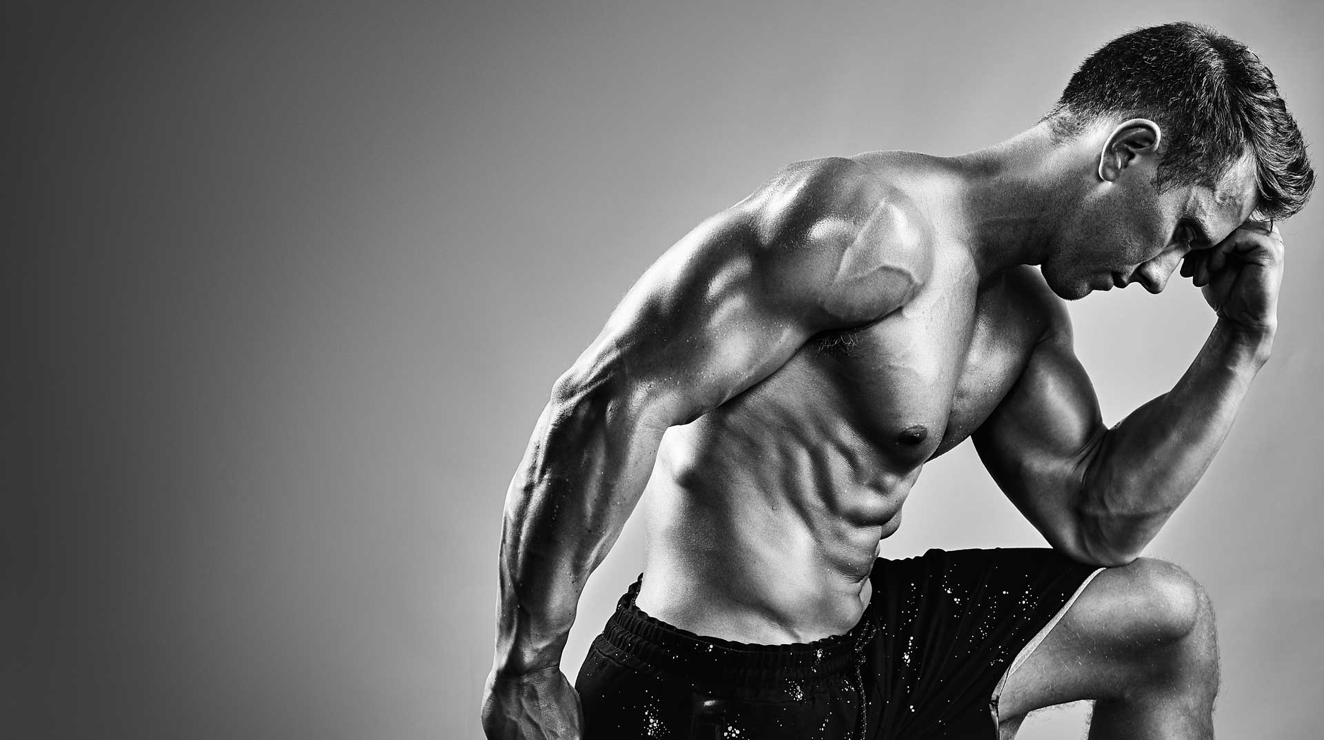 Black and white portrait of muscular bodybuilder with defined abs