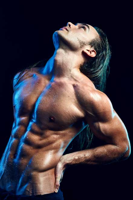 Bodybuilder with perfect abs in studio photo shoot