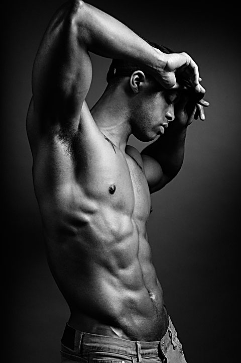Male fitness model lifts arms and flexes torso. Black and white photo with high contrast lighting. Photo by Antonio Carrasco.