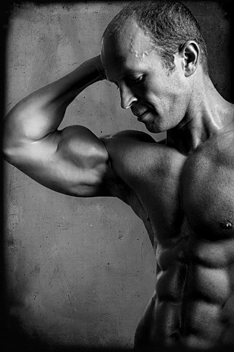 Bodybuilder flexes bicep for fitness photography shoot in Los Angeles