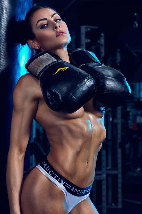 Fitness model Stephanie Marie leans against punching bag in boxing gym