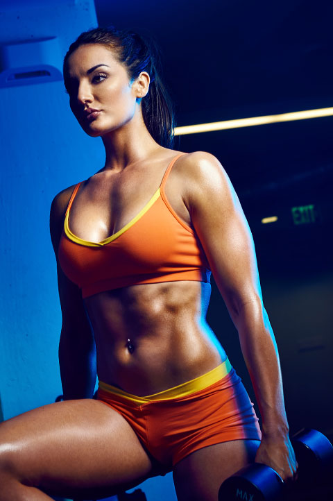 Model and Personal Trainer Whitney Johns wears activewear while lifting weights