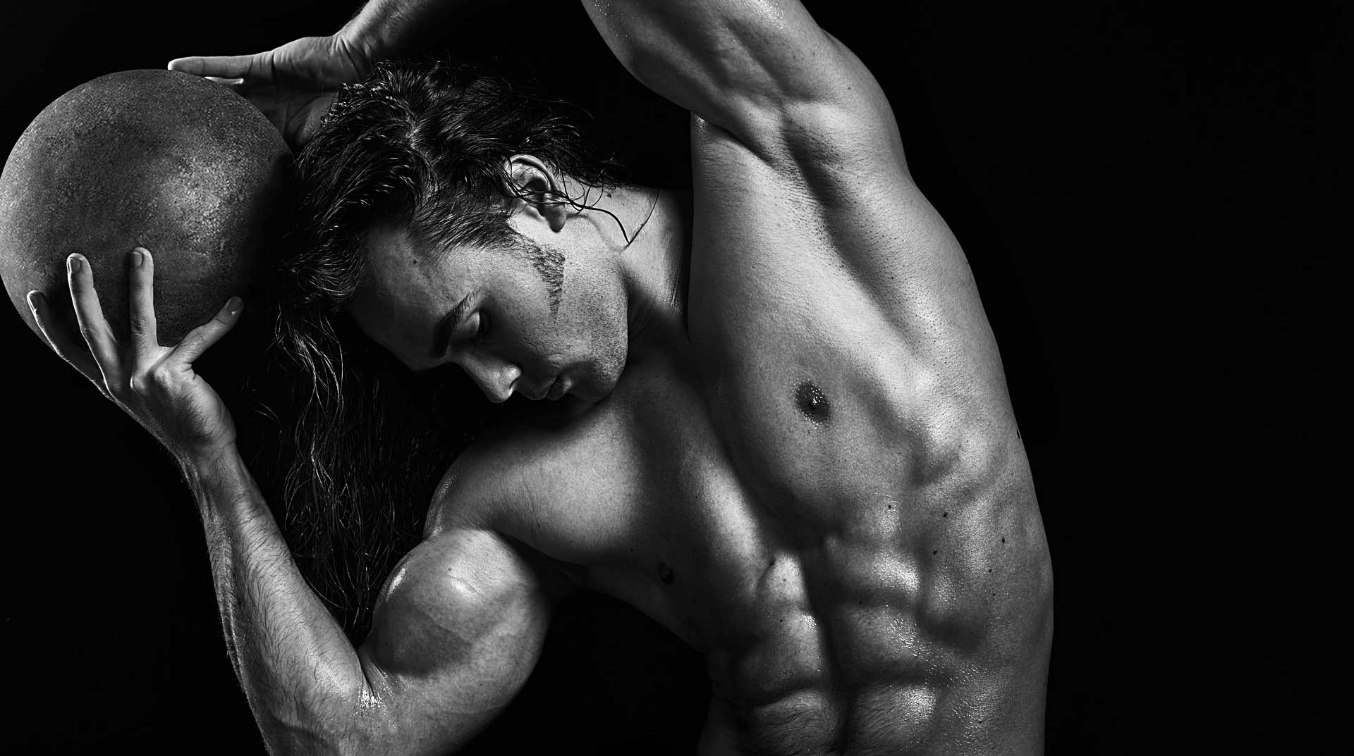 Black and white portrait of bodybuilder holding medicine ball